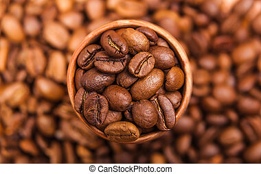 black coffee beans in a wooden cup