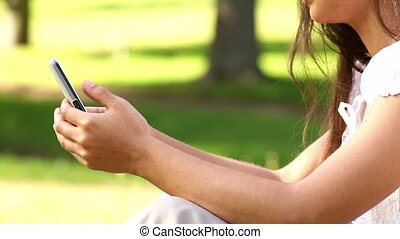 Pretty girl sitting on the grass texting