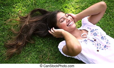 Pretty girl lying on the grass listening to music