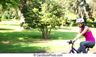 Fit girl going for a bike ride in the park on a sunny day