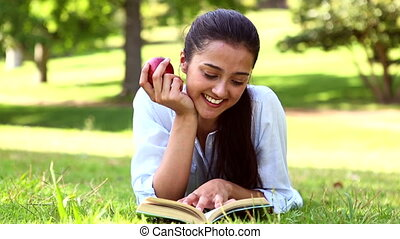 Pretty girl lying on the grass reading