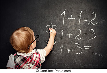 baby girl pupil draws a chalk on blackboard - baby girl...