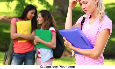 Blonde student being bullied by her peers on a sunny day