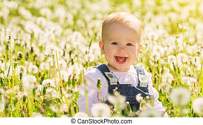 happy baby girl on  meadow with white flowers  on the nature