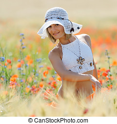 young beautiful woman on golden wheat field in summer
