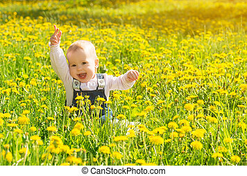 Beautiful happy little baby girl sitting on a green meadow...