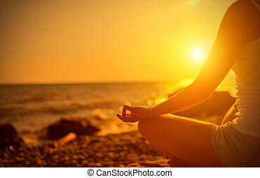 hand of woman meditating in a yoga pose on beach at sunset -...