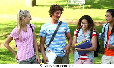 Happy students smiling and chatting on a sunny day