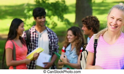 Student smiling at camera with friends - Student smiling at...