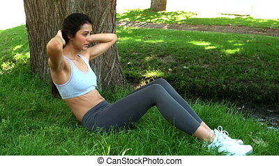 Fit woman doing sit ups on the grass in slow motion