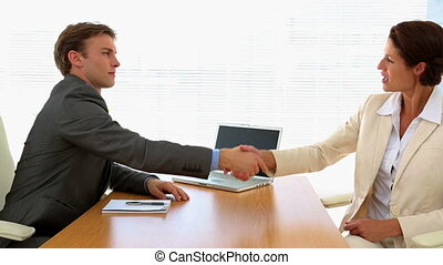 Business people shaking hands at a desk - Business people...