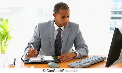 Businessman working at his desk and writing in diary in his...