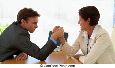 Business people arm wrestling at a desk