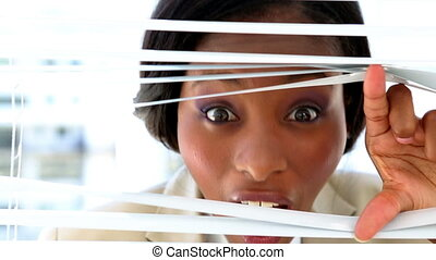 Businesswoman looking through blinds in the office