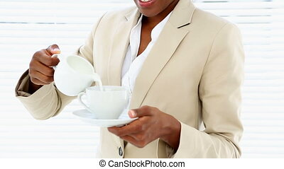 Businesswoman pouring milk into her cup in the office