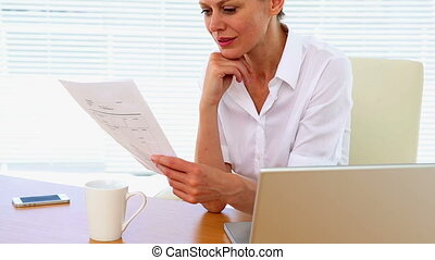 Businesswoman reading a document - Description:...