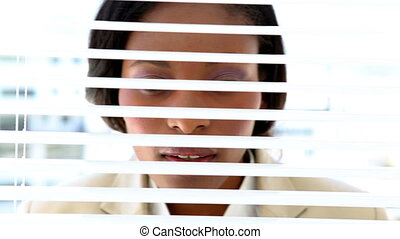 Businesswoman looking through blinds - Businesswoman looking...