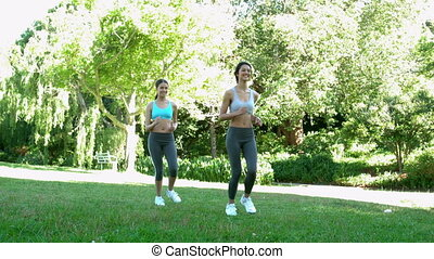 Fit friends running together in the park