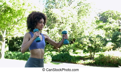 Fit brunette working out with dumbbells in the park in slow...