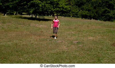 Fit woman sprinting past the camera in slow motion
