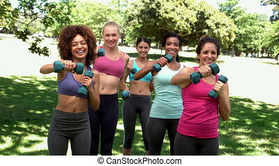 Fitness class working out together with dumbbells in the...