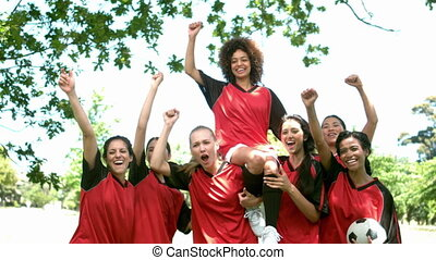 Female football team celebrating a win in the park in slow...