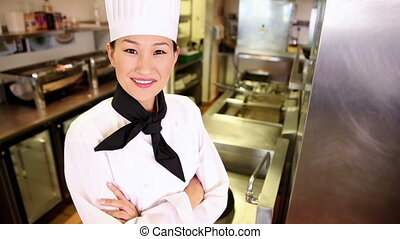 Happy chef smiling at camera in commercial kitchen