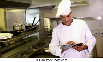 Handsome chef using tablet pc in commercial kitchen