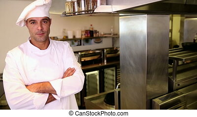 Handsome chef smiling at the camera in commercial kitchen