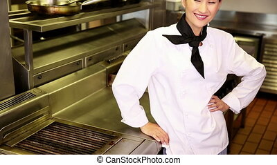 Happy chef smiling at camera beside the stove in commercial...