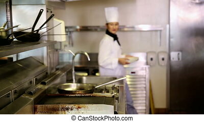 Asian chef putting away stack of plates in commercial...