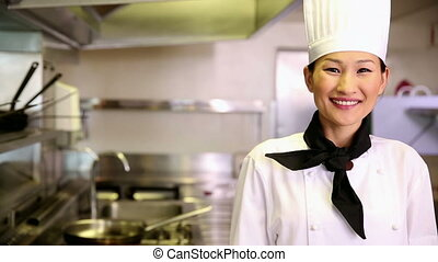Happy chef smiling at camera holding her hand out in...