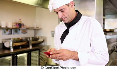 Handsome chef sending a text message in commercial kitchen