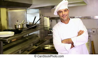 Handsome chef making ok sign to camera in commercial kitchen...