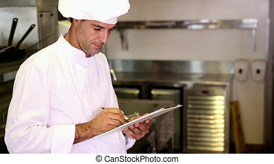 Handsome chef writing on clipboard in commercial kitchen