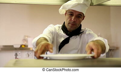 Handsome chef putting away plates in commercial kitchen