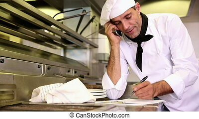 Handsome chef writing on clipboard while talking on phone in...