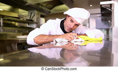 Handsome chef wiping down the counter in commercial kitchen...