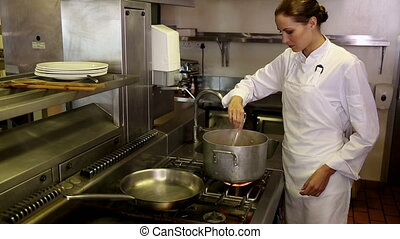 Pretty chef stirring a large pot in commercial kitchen
