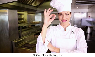 Pretty chef making ok sign to camera in commercial kitchen