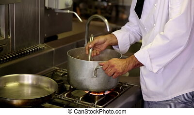 Handsome chef stirring a large pot in commercial kitchen