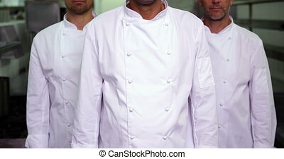 Three smiling chefs looking at camera making ok sign in a...