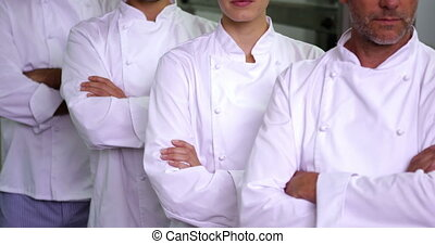 Four stern chefs looking at camera with arms crossed in a...