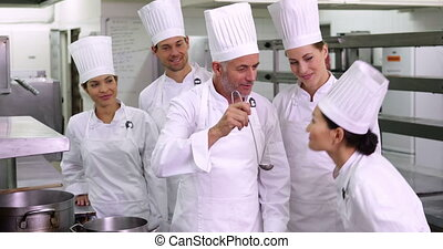 Chefs giving ok sign to camera - Team of chefs giving ok...