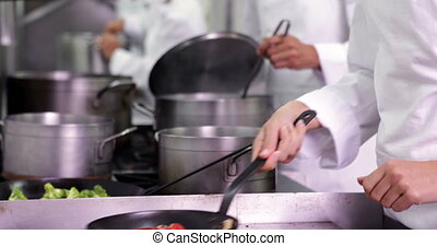 Chef frying vegetables then checking on colleague in a...