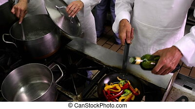Chef frying vegetables and adding olive oil to pan in a...