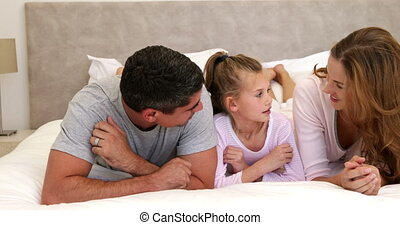 Parents and daughter lying on bed chatting at home in...