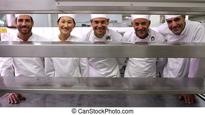 Smiling chefs standing in a row at order station - Smiling...