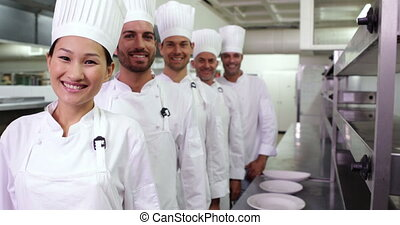 Smiling chefs standing in a line in a commercial kitchen