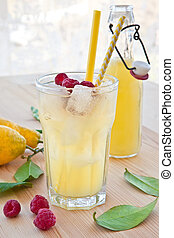 Cold lemonade with fresh lemons and raspberries